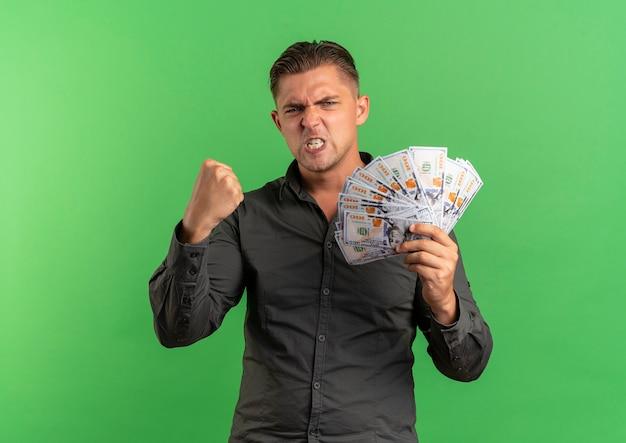 Jeune bel homme blond furieux détient de l'argent avec le poing levé isolé sur un espace vert avec copie espace