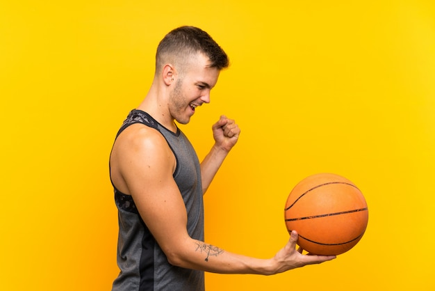 Jeune bel homme blond tenant un ballon de basket sur un mur jaune isolé célébrant une victoire