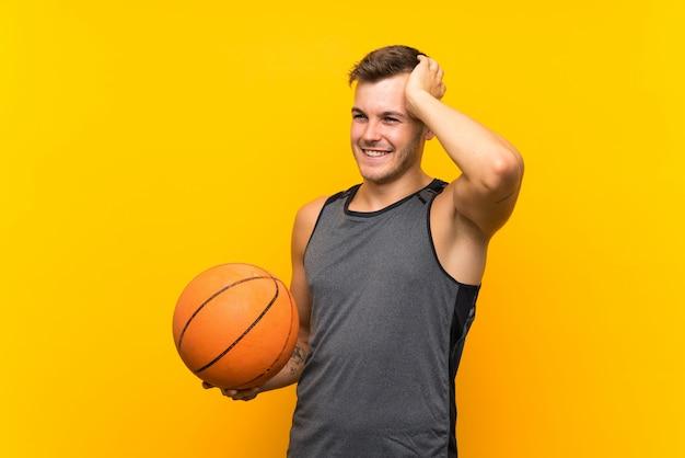 Jeune bel homme blond tenant un ballon de basket a réalisé quelque chose et a l'intention de la solution