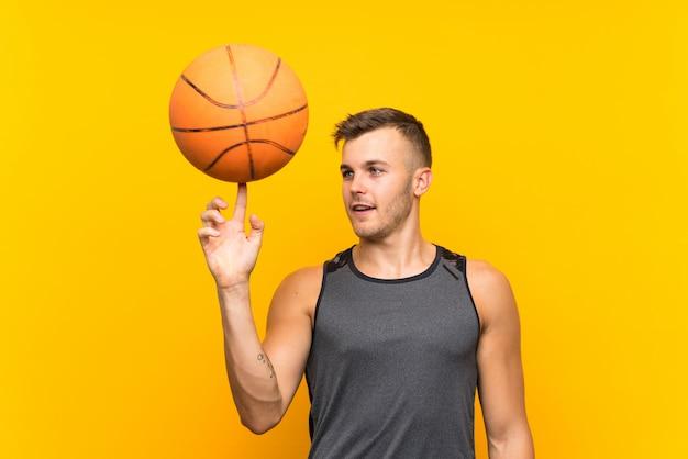 Jeune bel homme blond tenant un ballon de basket