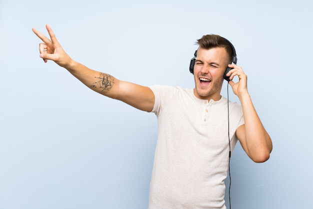 Jeune bel homme blonde sur un mur bleu isolé, écouter de la musique avec des écouteurs