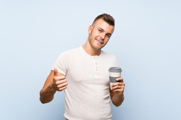 Jeune bel homme blonde sur mur bleu isolé, tenant une tasse de café