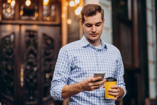Jeune bel homme, boire du café à l'extérieur