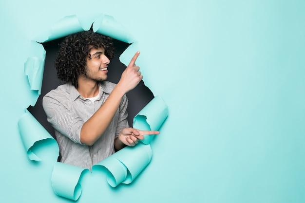 Jeune bel homme bouclé pointé sur le côté du trou sur du papier vert
