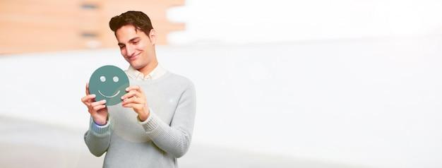 Jeune bel homme bronzé avec une émoticône smiley