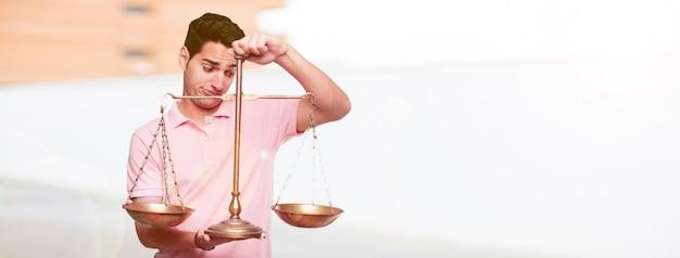 Jeune bel homme bronzé avec un équilibre ou une échelle de justice