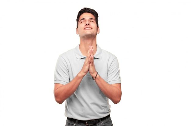 Jeune bel homme bronzé priant d'une manière sainte, mendiant