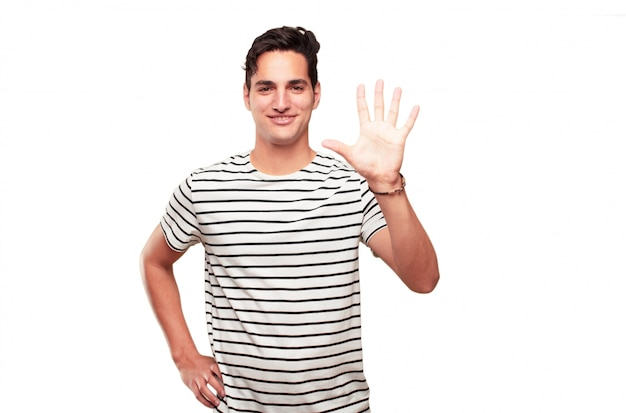Jeune bel homme bronzé souriant et regardant satisfait et heureux, comptant le numéro cinq avec les doigts