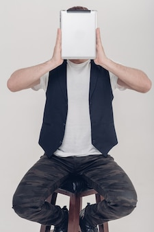 Jeune bel homme brune à la barbe en chemise blanche et gilet noir tenant une tablette devant son visage sur fond gris