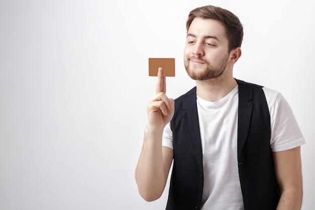 Jeune bel homme brune avec une barbe dans une chemise blanche et un gilet noir montrant une carte de crédit en plastique et souriant