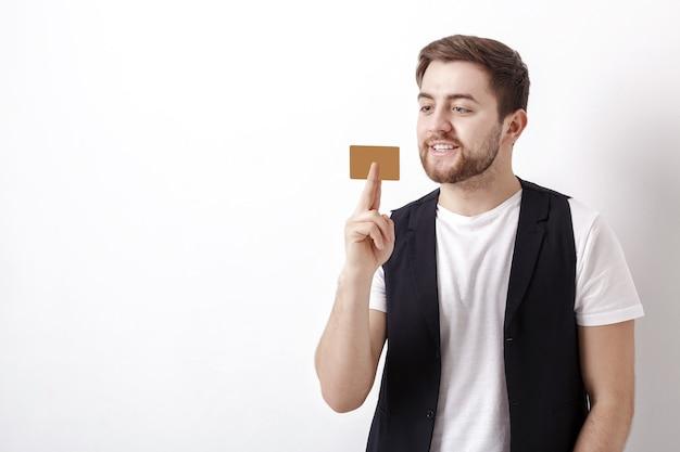 Jeune bel homme brune avec une barbe dans une chemise blanche et un gilet noir tenant une carte de crédit en plastique et souriant