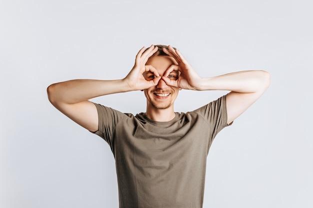 Jeune bel homme brunet avec barbe dit ok et clins d'oeil sur fond blanc isolé