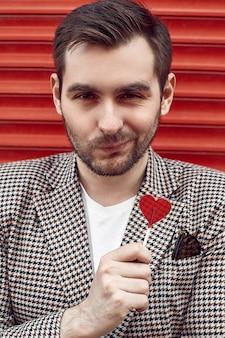 Jeune bel homme brutal dans un costume de mode près de la porte rouge