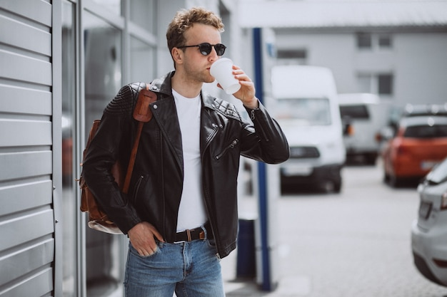 Jeune bel homme buvant du café dans la rue