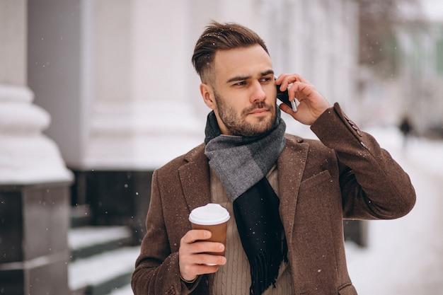 Jeune bel homme buvant du café et parler au téléphone