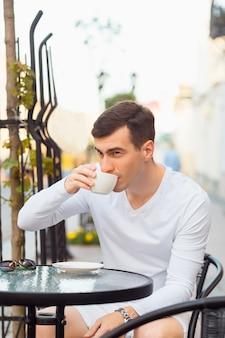 Jeune bel homme buvant du café