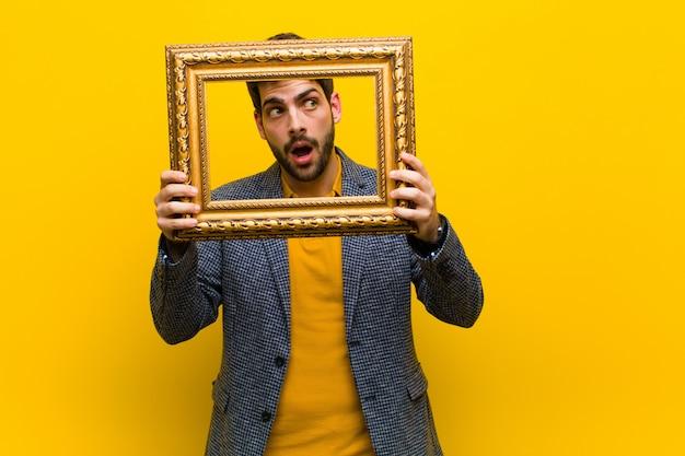 Jeune bel homme avec un cadre baroque contre backgroun orange