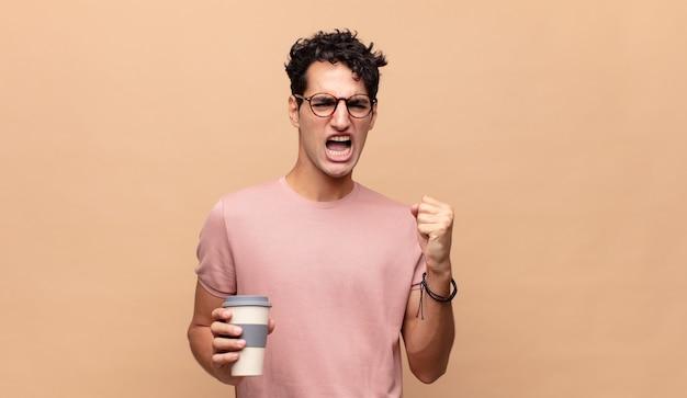 Jeune bel homme avec un café en criant agressivement avec une expression de colère ou avec les poings fermés célébrant le succès