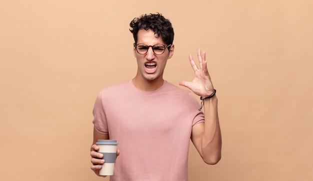Jeune bel homme avec un café hurlant avec les mains en l'air, se sentant furieux, frustré, stressé et bouleversé