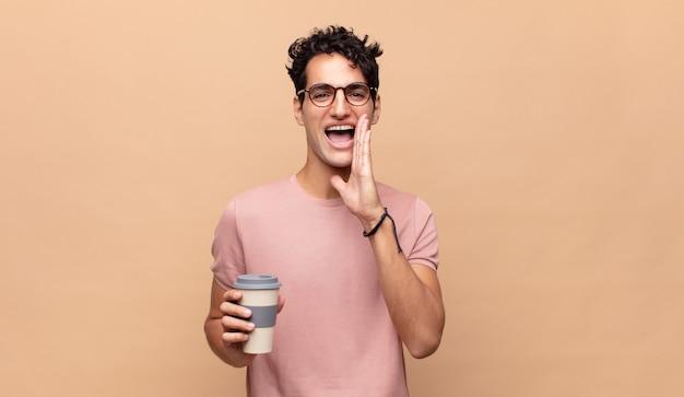 Jeune bel homme avec un café se sentant heureux, excité et positif, donnant un grand cri avec les mains à côté de la bouche, appelant