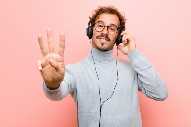 Jeune bel homme avec un casque contre le mur plat rose