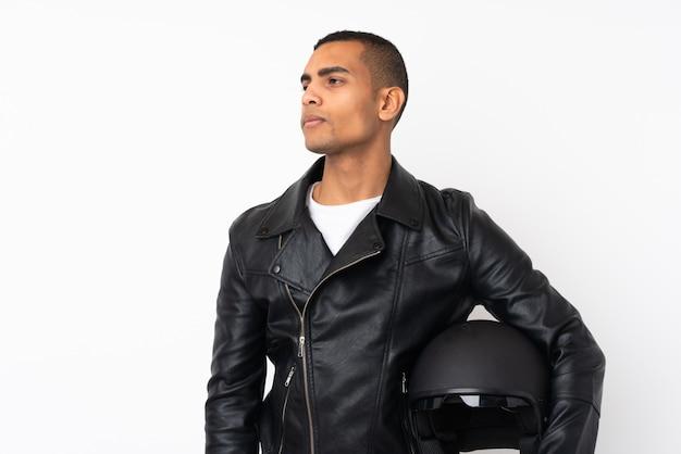 Jeune bel homme avec un casque de moto sur le mur blanc isolé côté regardant