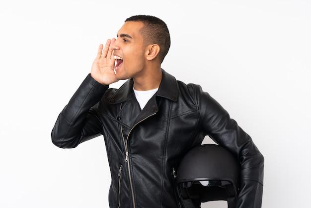 Jeune bel homme avec un casque de moto sur un mur blanc isolé criant avec la bouche grande ouverte