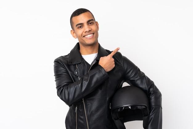 Jeune bel homme avec un casque de moto sur le mur blanc isolé pointant le doigt sur le côté