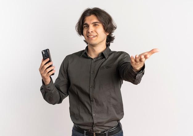 Jeune bel homme caucasien agacé tient le téléphone et les points à la caméra isolé sur fond blanc avec copie espace