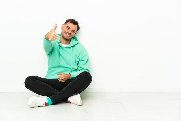Jeune bel homme caucasien assis sur le sol avec les pouces vers le haut parce que quelque chose de bien s'est passé