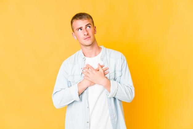 Jeune bel homme caucasien a une expression amicale, appuyant sur la paume de la main contre la poitrine. concept d'amour.