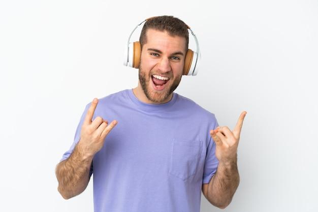 Jeune bel homme caucasien isolé écoutant de la musique faisant un geste rock
