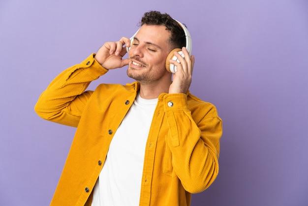 Jeune bel homme caucasien isolé sur l'écoute de la musique et du chant