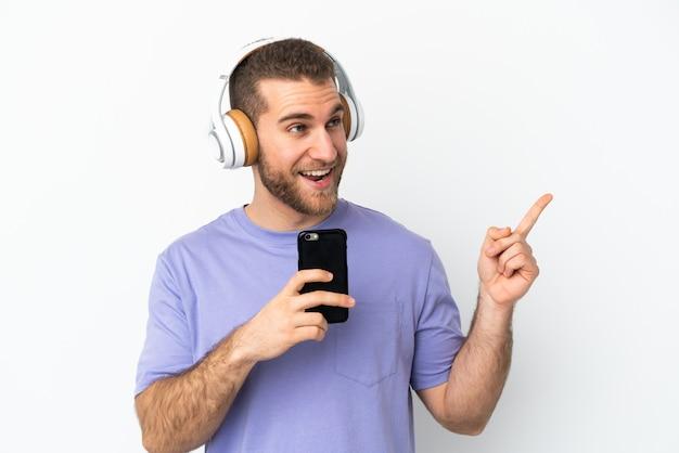 Jeune bel homme caucasien isolé écouter de la musique avec un mobile et chanter