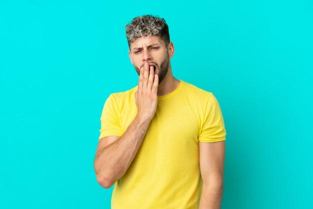 Jeune bel homme caucasien isolé sur fond bleu bâillant et couvrant la bouche grande ouverte avec la main