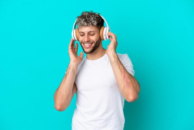 Jeune bel homme caucasien isolé sur fond bleu, écouter de la musique et chanter