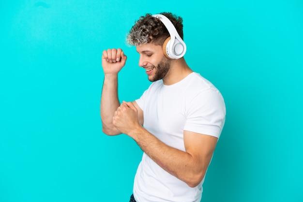Jeune bel homme caucasien isolé sur fond bleu, écouter de la musique et danser