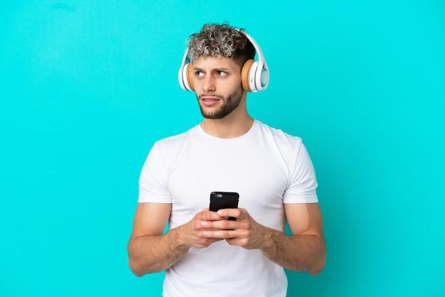 Jeune bel homme caucasien isolé sur fond bleu, écouter de la musique avec un mobile et penser