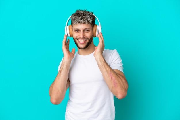 Jeune bel homme caucasien isolé sur fond bleu, écouter de la musique