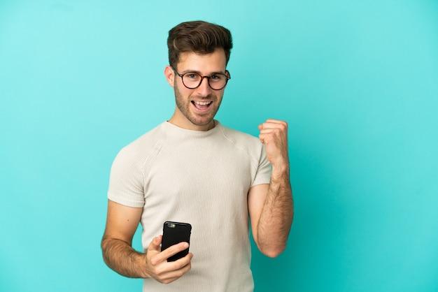 Jeune bel homme caucasien isolé sur fond bleu avec téléphone en position de victoire