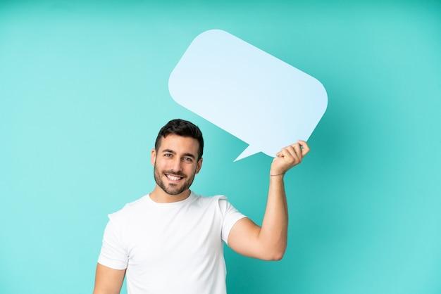 Jeune bel homme caucasien isolé sur fond bleu tenant une bulle de dialogue vide