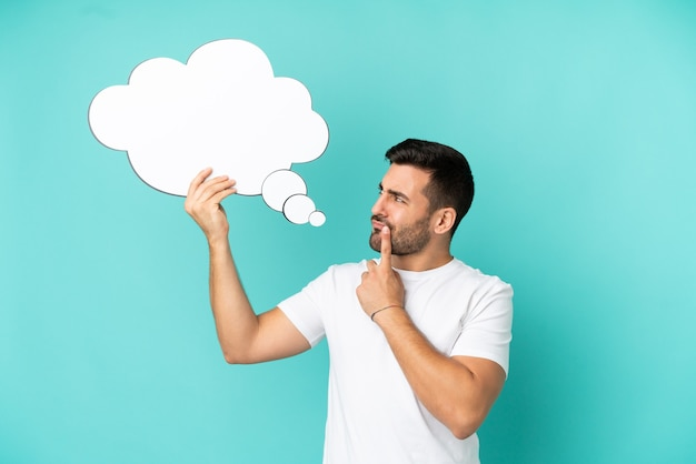 Jeune bel homme caucasien isolé sur fond bleu tenant une bulle de pensée