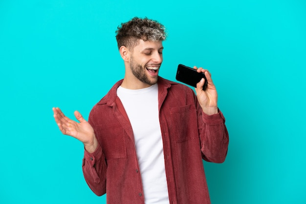 Jeune bel homme caucasien isolé sur fond bleu utilisant un téléphone portable et chantant