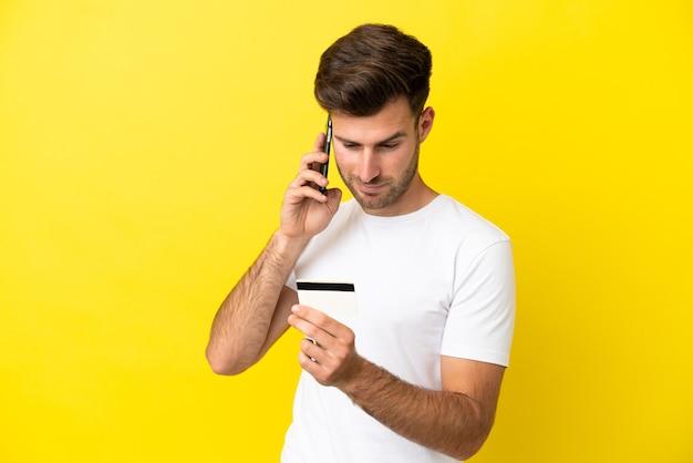 Jeune bel homme caucasien isolé sur fond jaune achetant avec le mobile avec une carte de crédit