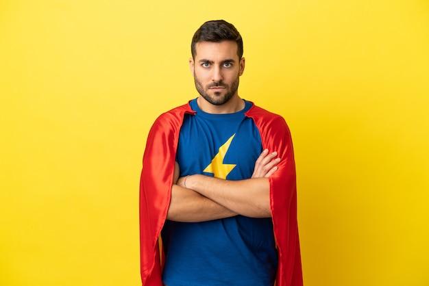Jeune bel homme caucasien isolé sur fond jaune en costume de super-héros avec les bras croisés