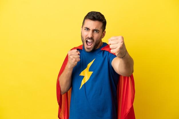 Jeune bel homme caucasien isolé sur fond jaune en costume de super-héros et combats