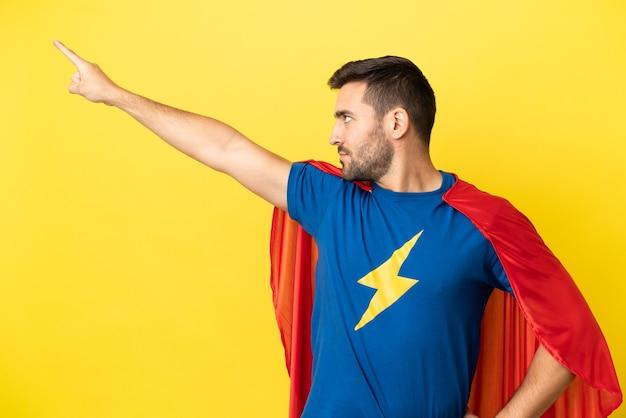 Jeune bel homme caucasien isolé sur fond jaune en costume de super-héros avec un geste fier