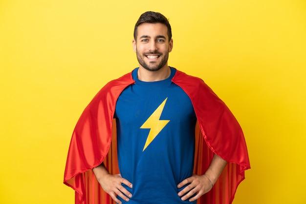 Jeune bel homme caucasien isolé sur fond jaune en costume de super-héros posant avec les bras à la hanche et souriant