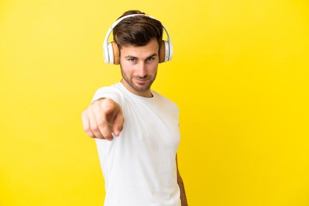 Jeune bel homme caucasien isolé sur fond jaune, écoutant de la musique et pointant vers l'avant