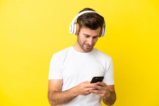 Jeune bel homme caucasien isolé sur fond jaune, écoutant de la musique et regardant vers le mobile